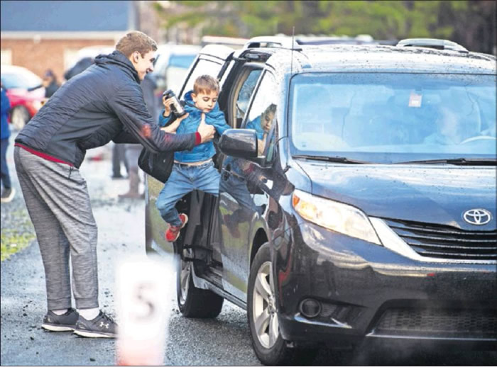 Elon Elementary School kindergartner Jonathon Stansberry gets a lift out of the backseat from Elon