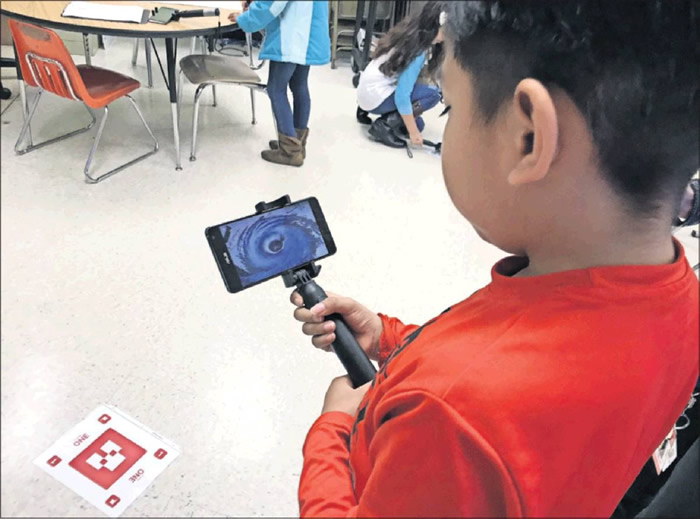 Christian Canar, 8, watches a hurricane rotate on the classroom floor using Google's augmented real