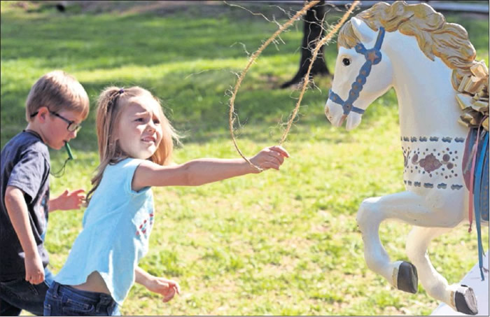 Anistyn Branch, 6, successfully throws a lasso onto a carousel horse at the first annual Western Ala