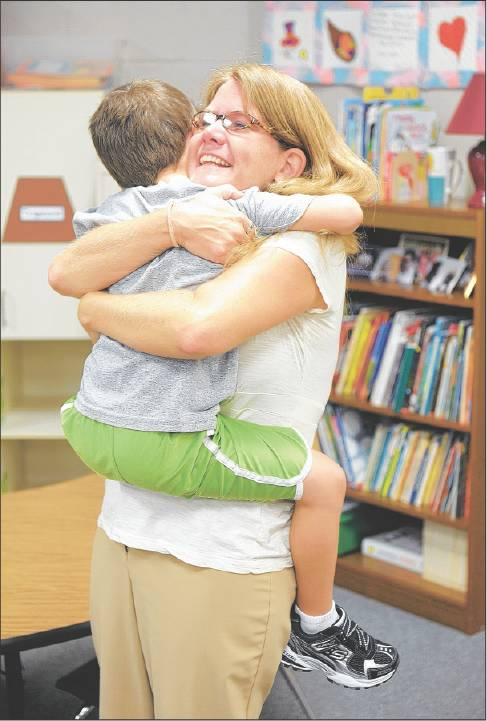 Dottie Small hugs her son Jack, 5, in Tammy Teal's kindergarten class prior to the start of the first day of school at Garrett Elementary in Mebane.