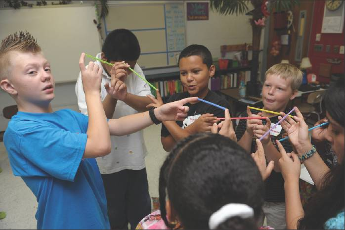 Rising eighth-grader Ryan Haneline, left, engages incoming sixth-graders, from left, Lennon Sosa, Mason Leath, Hunter Fankhauser and Marisela Flores with straws to demonstrate teamwork Thursday during Graham Middle School's Sixth Grade Survival Camp. The one-day event is hosted by eighth-graders and is intended to ease the transition into middle school for sixth-graders.