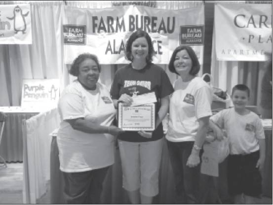 "From left are Alamance County Womens committee member Lillie Enoch; Jennifer Tripp, teacher at Garrett Elementary; and Womens committee member Donna Vines and grandson Brice Via. They were present when Tripp was honored for winning the ""Ag in the Classroom"" grant for her idea of a school strawberry garden and a cart in which students can grow plants. Ag in the Classroom, ""Going Local,"" provides grants valued up to $500 for teachers who integrate agriculture lessons into classroom studies."