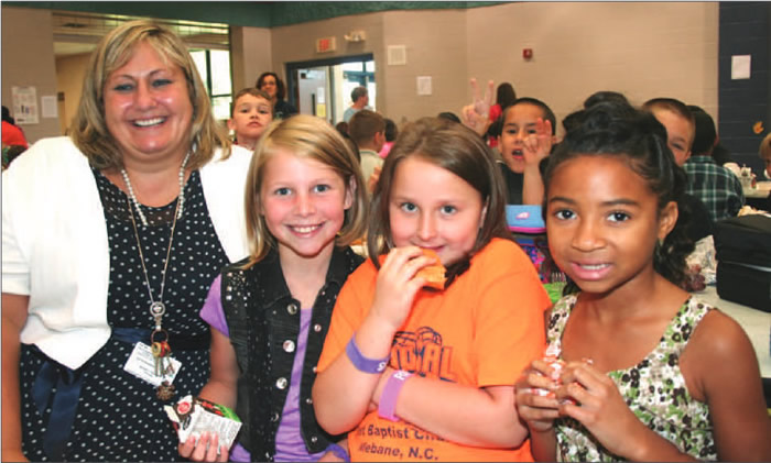 "Here in the lunchroom at Garrett, Principal Michelle Ammann (left) gathers some third-grade Gators together to talk about what they look forward to at the swamp. (L-r) Zoe Schuhler, Victoria Howard, and Dori Paylor say they are excited about ""a good school year""."
