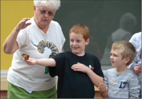 Alexander Wilson Elementary School teacher assistant Kay Story, left, and kindergartner Kaiden Simons, right, watch Monday as third-grader Lane Whitfield releases a monarch butterfly next to the school's butterfly garden.