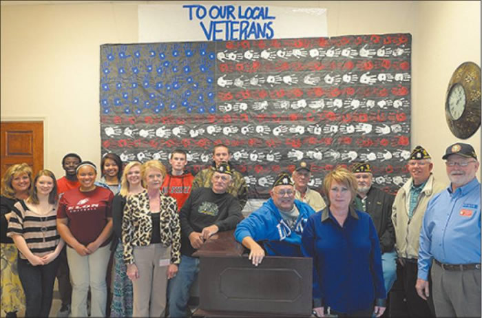 Students in Joy Walker's civics, economics and 1960s classes created a large flag with hand prints to honor local veterans. The flag now resides inside the Alamance County Veterans Service Office in Graham. Some of the students from Walker's classes were on hand Thursday along with local veterans.