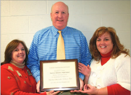 Eastern Alamance High School Principal Dave Ebert (center) celebrates the success of education with academic coach Sherri Slade (left) and Social Studies teacher and department chair Joy Walker (right) on Monday. They are holding up Eastern's plaque, the school having been recognized for a prestigious award and academic success from the Piedmont Triad Education Consortium last Friday.