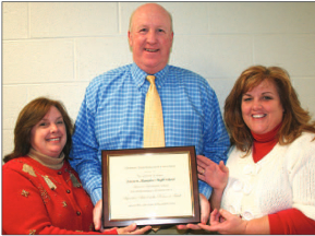Eastern Alamance High School principal Dave Ebert (center) congratulates his staff Monday evening at the school board's recognition of Eastern as a Signature School. Here he holds up the plaque from the Piedmont Triad Education Consortium with teachers Sherri Slade (left) and Joy Walker (right).