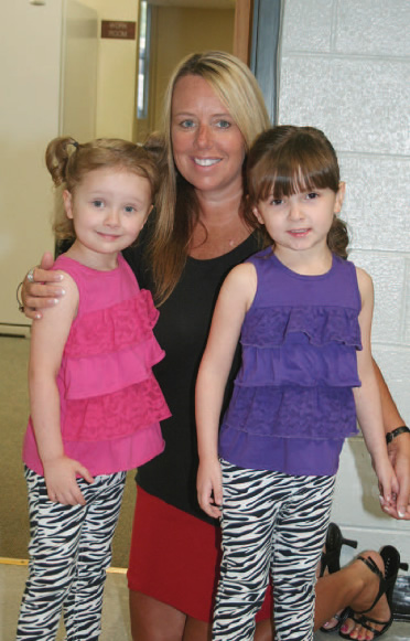 Academic Coach Beth Curasi welcomes twins Breana (left) and Jayden Delosh (right) to their first day in kindergarten at E. M. Yoder Elementary in Mebane.