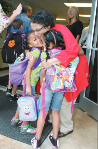 Rhonda Howard welcomes twins Morgan and Megan Heath back to E. M. Yoder on day one of the new school year.