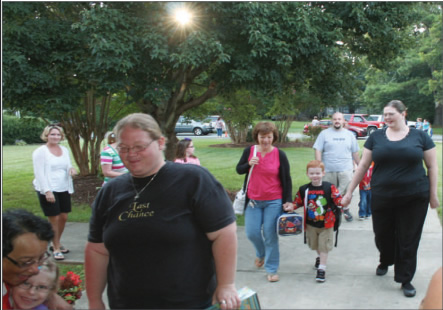 Parents and students walk to the school on the first day of the school year at E. M. Yoder Elementary. Many of the children live within a short walking distance of the school.