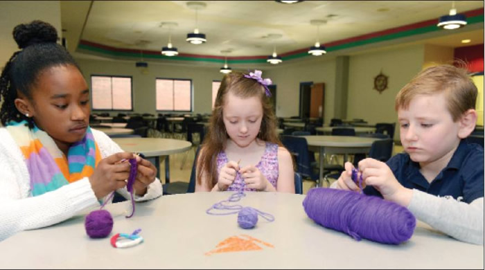 Smith Elementary students, from left, Olivia McCoy, 9, Corinna Workman, 10, and her brother Holt Workman, 7, knit i-cord bracelets Friday. Corinna Workman came up with the idea to make bracelets to sell to make money for The Alzheimer's Association in honor of her great-grandmother, who suffers from Alzheimer's disease. For more information or to order a bracelet, email purplebracelets@gmail.com
