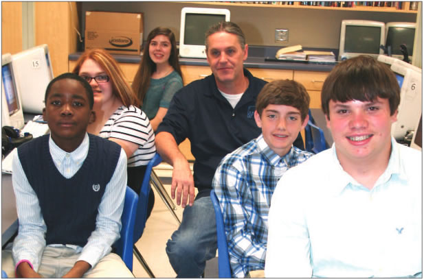 "With their teacher Chris Small (center), students gather in the computer lab at Woodlawn Middle School. They would be talking with a renown orthopedic surgeon, a ""virtual visit,"" through Skyping. More students would join them. Pictured are (l-r) Brian Corbett, Betty Baker, Louisa Seamster, Small, Jackson Hartley and Jacob Littell."