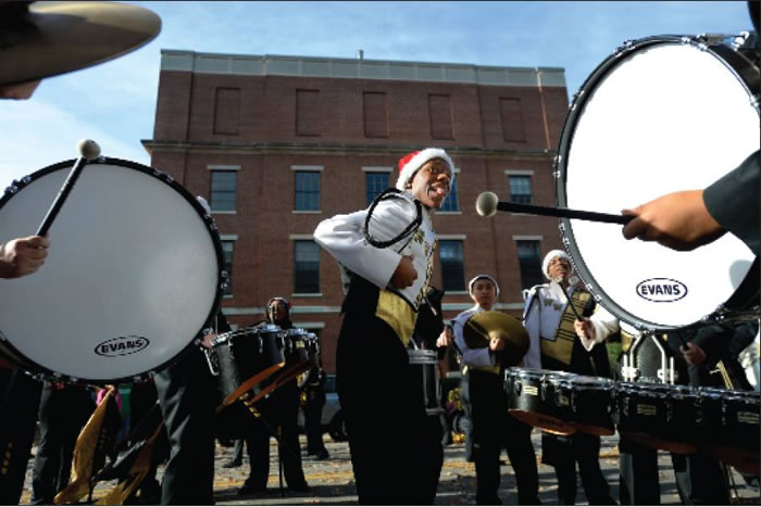 P.J. Graves, above, who plays the cymbals in the Williams High School band, dances in the center of the drumline as the band warms up Saturday before the Burlington Christmas Parade.