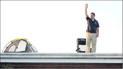 Alexander Wilson Elementary School Principal Dean Richardson waves to passers-by from the roof of the school.