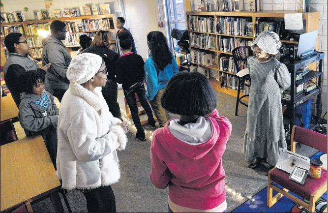 Destiny Currie reads information about Elizabeth Keckley. In all, 15 students portrayed historical figures. Like a real wax museum, the actors read their material only when their audience put a penny in a container in front of them. Proceeds from the event went toward the school's backpack program.