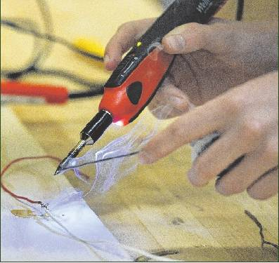 O'Brien solders a wire during the first day of the camp.