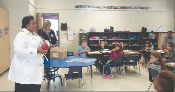 Hayden-Harman project coordinator Michele Davis and volunteers delivered personalized dictionaries to third graders at Mebane's E.M. Yoder Elementary on Monday, Oct. 19.