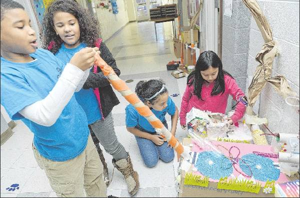 "From left, Haneef Rasheed, 8, Delanie Webb, 9, Janitzia Rodriguez, 10, and Abigail Gonzalez, 9, inspect their handmade candy-making devices. The fourth-grade students are reading ""Charlie and the Chocolate Factory"" and have created various rooms that would be inside the factory."