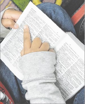 Above, a student cracks open his new dictionary.