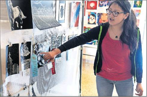 Anglela Romero, an Art 2 and 3 student at Graham High, points to her artwork on display at the Thursday, May 23, art show.