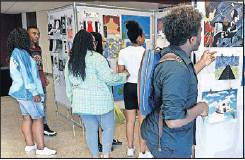 Graham High students view panels with artwork from Art 1 and Art 2 students in a show at the school on Thursday afternoon.