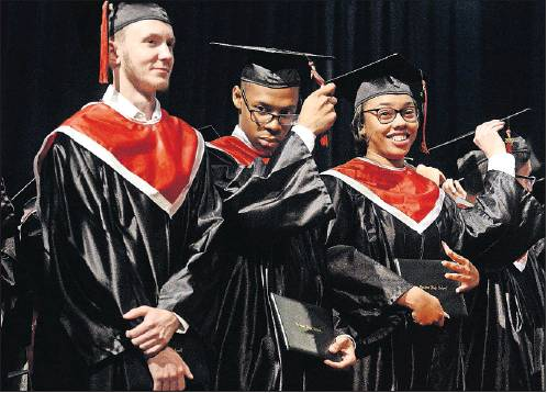 Graham High School graduates hold their diplomas and move their tassels Friday, June 14, at the Mebane Arts Center.
