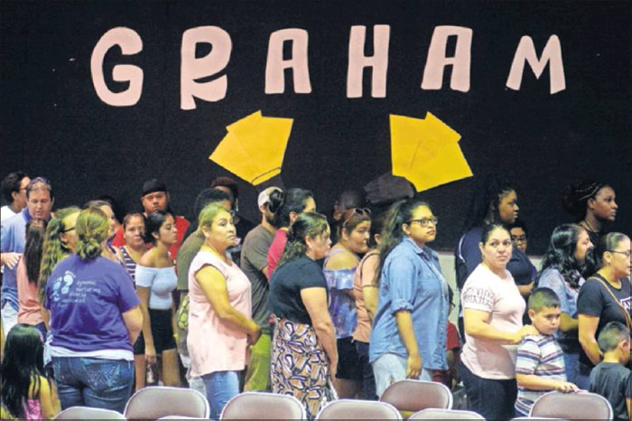 Parents with sixth-graders file from the Graham Middle School auditorium to meet teachers during the open house Wednesday evening, at this ABSS year-round school.