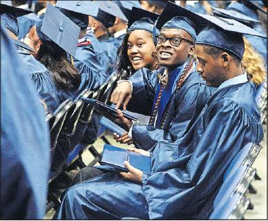 >A Cummings High School graduate points to his own diploma as fellow graduates return to their seats after crossing the stage during commencement Saturday, June 15, inside the fieldhouse at the Greensboro Coliseum.