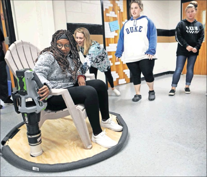 Jada Ramsey goes for a ride as Madysn Taylor pushes her on a hover chair at Southern Alamance Middle School on Nov. 5. The 8th grade career and technical education class have been building the device that uses a leaf blower to make it hover for the past two weeks.