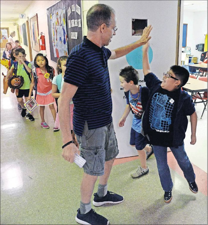 Second-grade substitute teacher Rob Gasparello receives a high-five as students leave for summer vacation Tuesday morning. Gasparello, a retired principal, taught at Elon Elementary from 1978 to 1981.