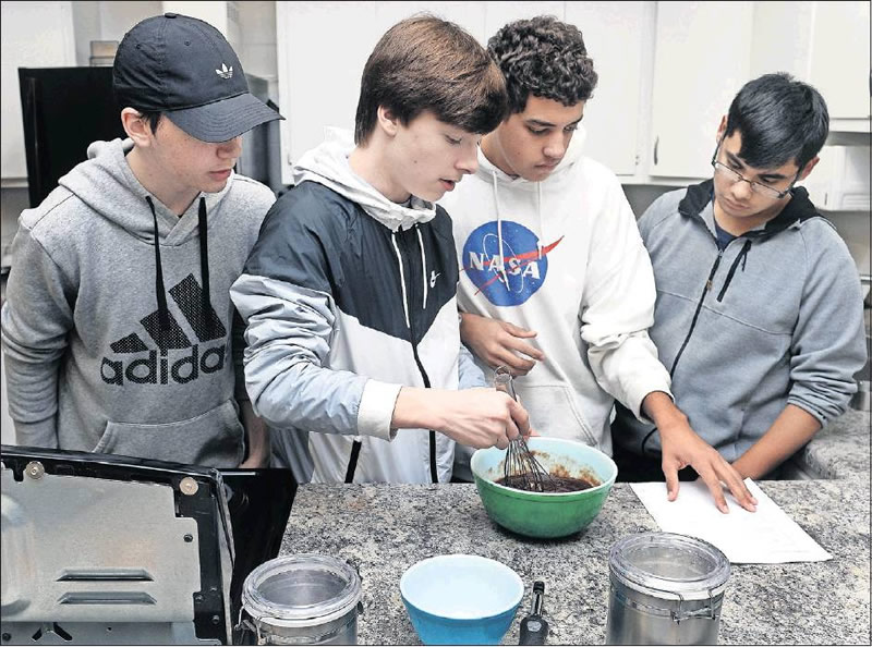 Western Alamance High School students Cameron Allen, London Hamlett, Adrian Boone, and Jonathan Lains stir batter to make brownies from scratch in the Foods 1 course taught by Amy Carter, the Family and Consumer Science instructor for the Career and Tech Education program.